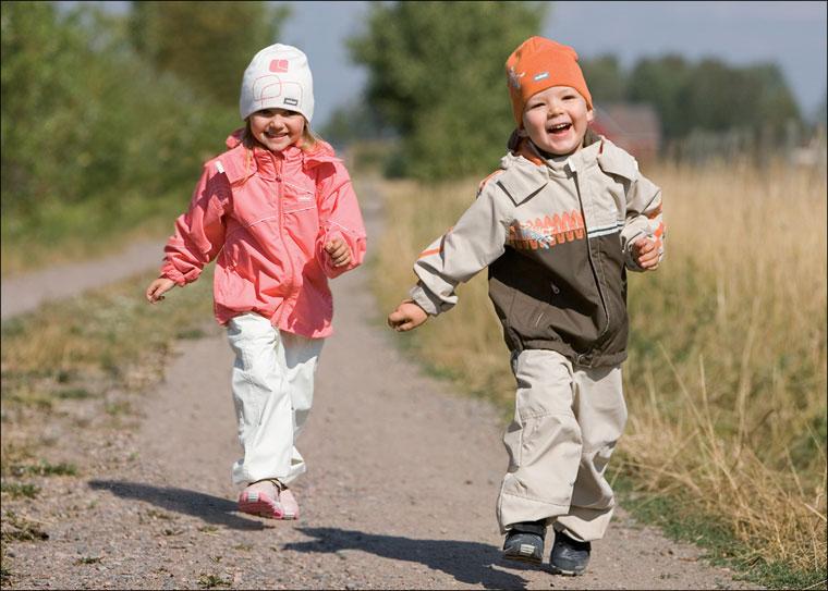 осень холодно тепло и хорошо одетые дети - девочка и мальчик - бегают по проселочной дороге