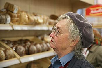 пенсионерка у прилавка с хлебом