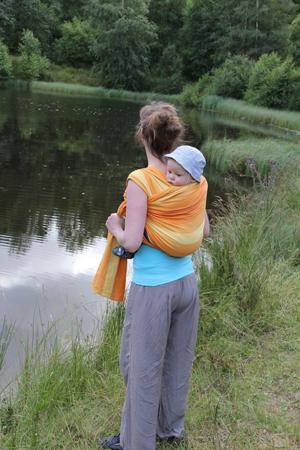 ребенок в слинге на спине у женщины