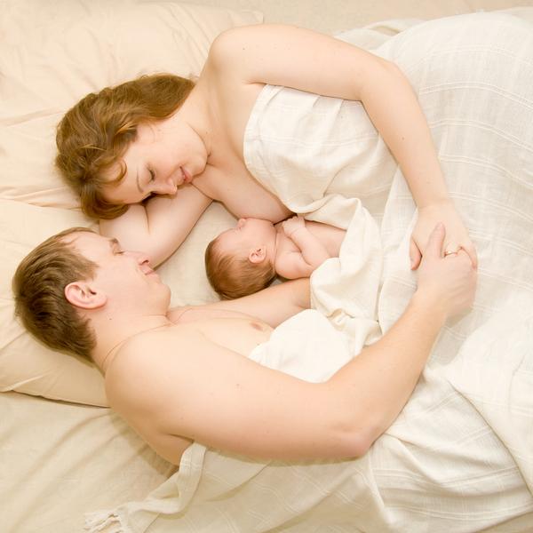 мама и папа на кровати между ними ребенок сосет грудь