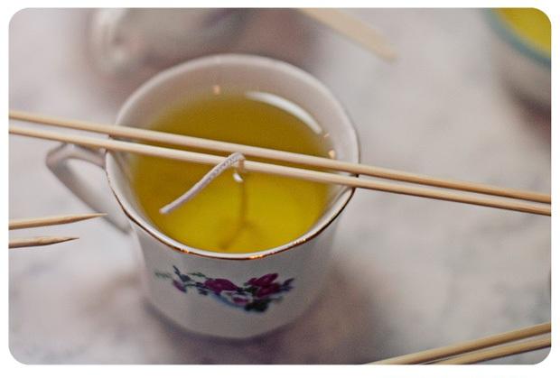 фитиль на шампуре опущен в воск в форме для свечи