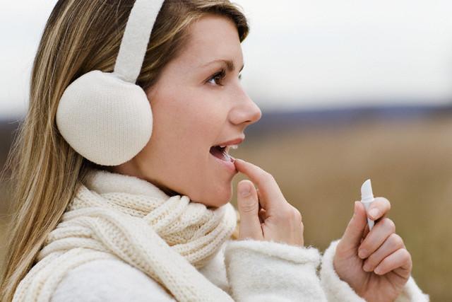 симпатичная девушка в белых наушниках на улице наносит бальзам на губы