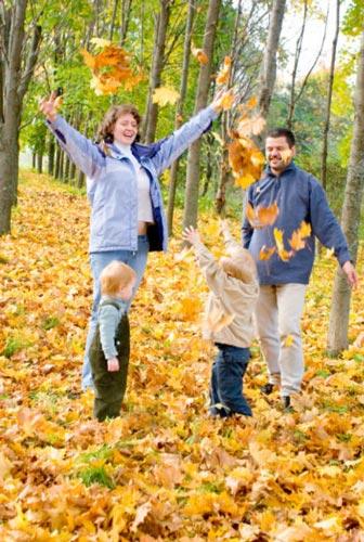 семья пама мама два ребенка играют желтыми яркими осенними опавшими листьями