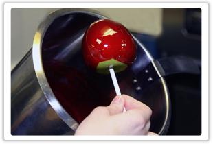 яблоко на деревянной палочке обмакивается в карамель шоколад