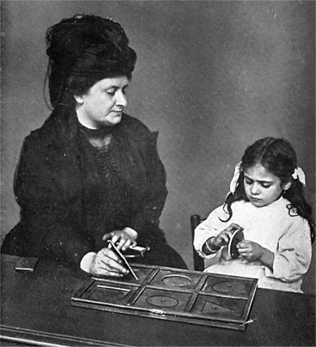 Монтессори сенсорная, здесь используется тактильный подход к выбору ежедневных детских рабочих принадлежностей, вроде столов с песком