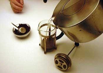 Залейте небольшое количество горячей воды из чайника в колбу – достаточно, чтобы смочить перемолотый кофе