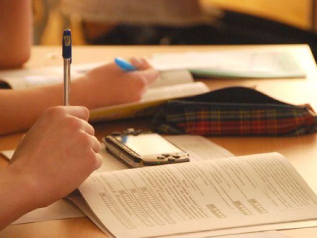 смартфон у школьницы на тетради ручка пишет за партой