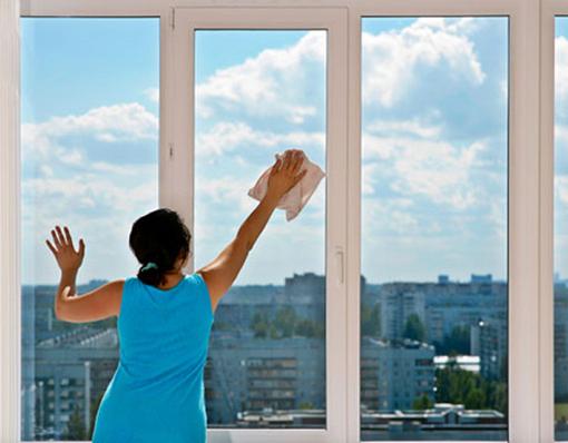 женщина моет пластиковое окно