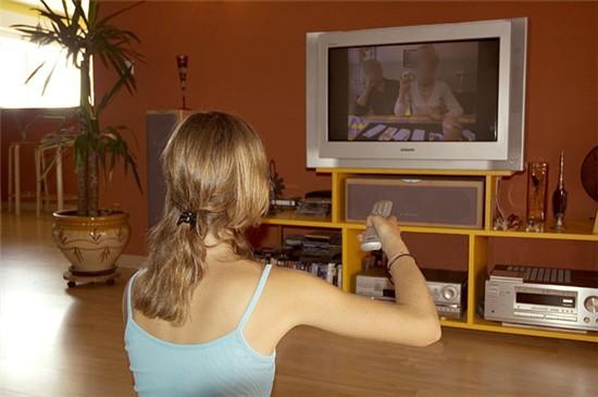 девушка сидит на полу с пультом смотрит телевизор переключает каналы