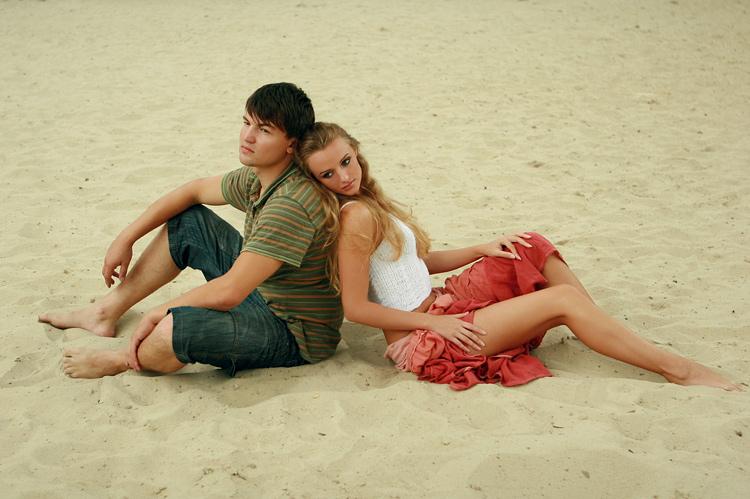 девушка и парень спина к спине сидят на песке