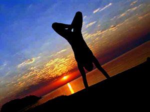Работа над собой самосовершенствование парень стоит на руках на закате около моря в позе лотоса