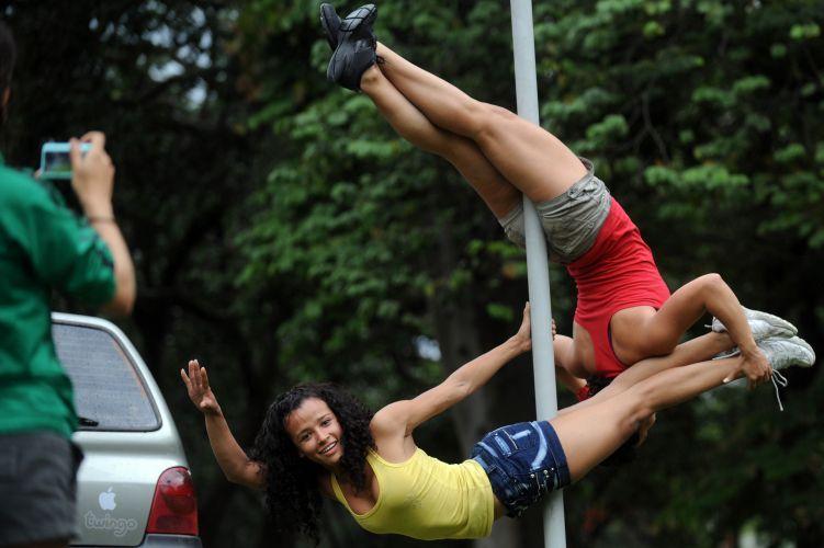 женщины девушки в спортивной маечке и шортах танцуют отплясывают на столбе шесте на улице
